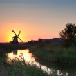 Shining windmill during sunrise over river — Stock Photo