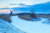 Windmill and frozen river in snow — Stockfoto