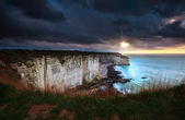 Sunshine and storm sky over cliffs in ocean — Foto Stock