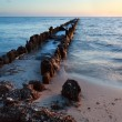 Old wooden breakwater in North sea at sunset — Stock Photo #42412173