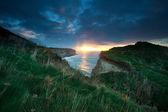 Sunset sunshine over cliffs in ocean — Foto Stock