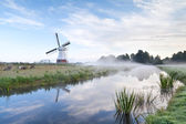 Dutch windmill by river in morning — Stockfoto