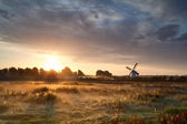 Misty sunrise over meadow with windmill — Stock Photo