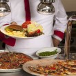 Chef standing behind burger,spaghetti and pizza station — Stock Photo