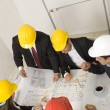 Stock Photo: Above view of architects sitting at table and discussing des