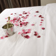 Hotel room with big bed and red flowers — Stock Photo