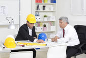 Architects sitting at table and looking at a project — Stock Photo