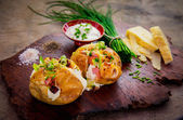 Rustic baked Potato with a variety of toppings — Stock Photo
