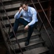 Man in shirt sitting on stairs — Stock Photo