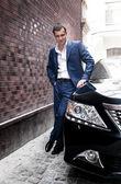 Man in suit posing near car — Stock Photo