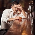 Man in white shirt sitting near bar desk with whiskey — Stock Photo