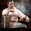 Man in shirt sitting at the table and smoking — Stock Photo