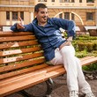Macho man sitting on bench — Stock Photo