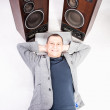 Man lying on floor near two big loudspeakers — Stock Photo #32875257