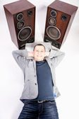 Man lying on floor near two big loudspeakers — Stock Photo