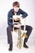 Musician sitting on chair and holding saxophone — Stock Photo