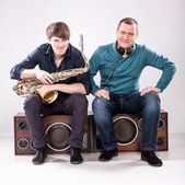 Saxophonist and dj sitting on loudspeaker — Stock Photo