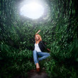 Girl sitting in tunnel from plants — Stock Photo