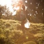 dívka procházky v parku v sluneční paprsky — Stock fotografie