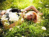Girl lying on grass with flowers — Zdjęcie stockowe
