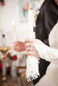 Bride and groom holding candles on wedding — Stock Photo