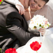 Bride hugging with groom behind red tulips — Stock Photo
