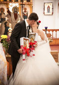 Married couple kissing in orthodox church — Stock Photo