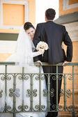 Groom sitting on railing while bride hugging him — Stock Photo