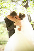 Groom and bride passionately kissing in park — Stock Photo