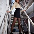Girl with long legs and short dress posing on stairway — Stock Photo