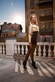 Girl in short dress posing against rooftops — Stockfoto