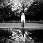 Woman standing near big oak tree near lake — Stock Photo #33241593