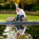 Woman sitting on rock under tree near big lake — Stock Photo