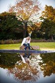 Блондинка женщина, сидя на скале под дубом — Стоковое фото
