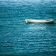 Old white fisherman boat floating on waves — Stock Photo