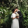 Bride and groom kissing against big bush with flowers — Stock Photo #33374335