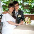 Bride and groom sitting in restaurant summer terrace — Stock Photo