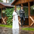 Newly married couple standing in wooden alcove in rainy weather — Stock Photo