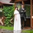 Groom and pregnant bride posing against wooden alcove — Stock Photo