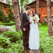 couple standing together in forest against wooden houses — Stock Photo