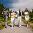 Stock Photo: Married couple running with friends in park alley