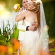 Bride with red dreadlocks hugging groom — Stock Photo