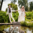 Groom holding brides hands and walking on bridge — Stock Photo