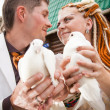 Bride and groom holding two pigeons close to each other — Foto de Stock