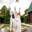 Married couple letting out two white pigeons — Stock Photo