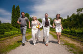 Married couple running with friends in park alley — Stock Photo