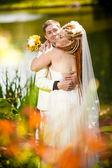 Bride with red dreadlocks hugging groom — Stock Photo