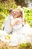 Newly married couple hugging on glade in park — Stock Photo