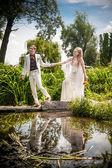 Groom holding brides hands and walking on bridge — Stockfoto