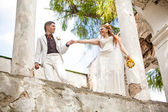 Newly wed couple holding hands and walking on bridge — Stock Photo